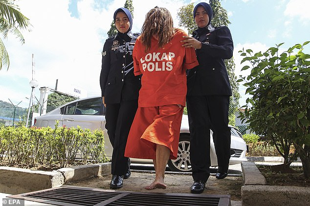 Samantha Jones is flanked by guards as she arrives barefoot to court wearing prison scrubs