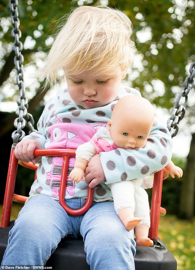 Izzy was captured by her father Dave Fletcher, 39, dosing on a playground swing when she was just 23 months old