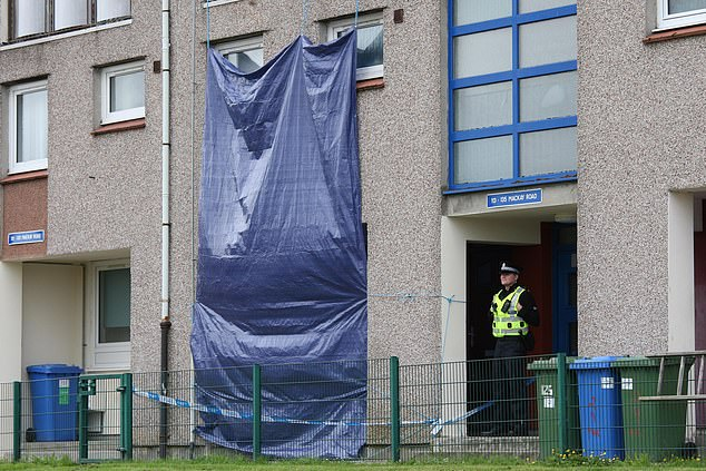 Forensic officers were seen going in and out of the property. A large blue tarpaulin was suspended from a balcony above the maisonette flat