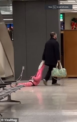 A dad was seen nonchalantly dragging his daughter through baggage claim by her hood