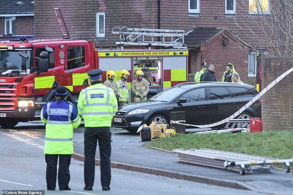 Firefighters and police officers form a guard of honour for the children as they are removed from the scene in Stafford by private ambulances this afternoon
