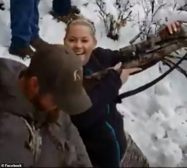 The woman appears overjoyed, having killed the bobcat during the recent hunt